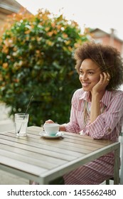 Attractive mixed race woman sitting in cafe and enjoying her coffee.