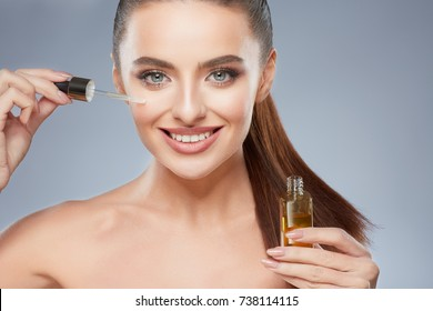 Attractive model with brown hair fixed behind, clean fresh skin, big eyes and naked shoulders posing at gray studio background, close up, portrait, holding face oil.