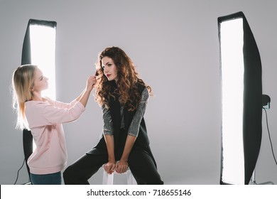 attractive model and hair stylist in photo studio with lighting equipment