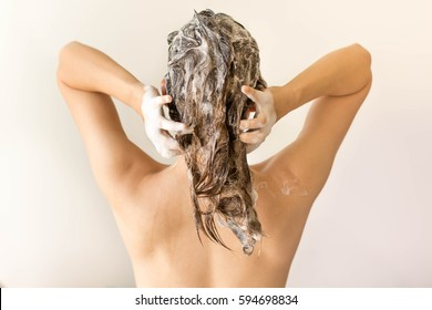 Attractive model shampooing her long hair from behind.