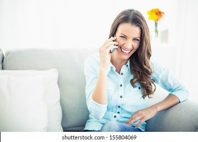 Attractive model sitting on cosy couch in bright living room having a phone call