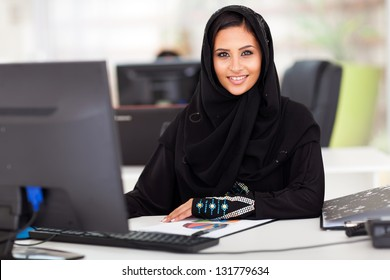 attractive modern Arabian businesswoman in traditional clothing working in office