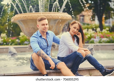 Attractive modern couple on a date is posing over city fountain.