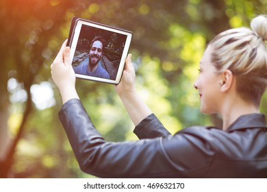 attractive, modern young couple having a video call over a tablet, outdoors on a sunny day. graded in an instagram style