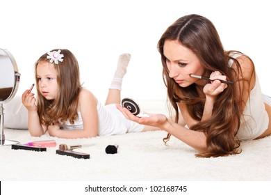 Attractive mother and daughter with cosmetics