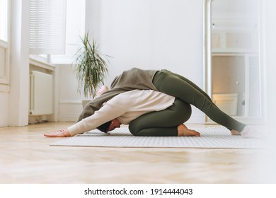 Attractive mother middle age woman and daughter teenager ptactice yoga together in bright room