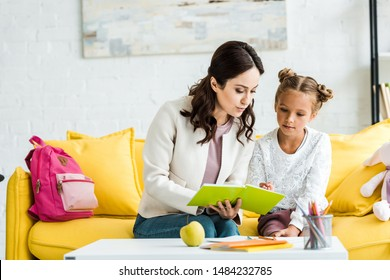 attractive mother reading book with cute daughter at home