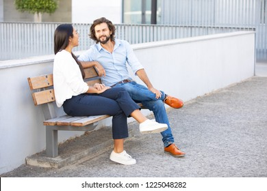 Attractive multiethnic businesspeople talking at sitting on bench near office building. Professional corporate couple on meeting in urban city. Teamwork concept