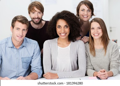 Attractive multiethnic group of young people posing grouped close together looking at the camera with warm friendly smiles