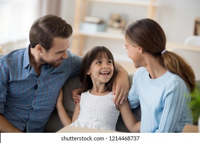 Attractive multi-ethnic young family with child sitting on sofa in living room at new home. Parents talking communicating with adorable small daughter feels happy excited enjoying free time together