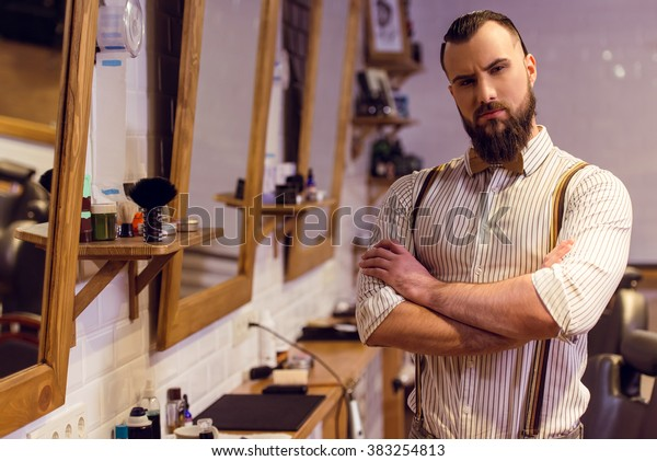 Attractive muscled bearded barber looking at camera while standing arms crossed in the barber shop