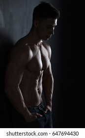 Attractive muscular body builder. Low key light