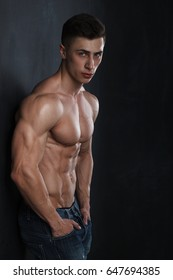 Attractive muscular body builder is posing in front of a black background