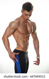 Attractive muscular body builder is posing in front of white background