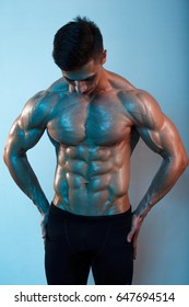 Attractive muscular body builder is posing in colored light.