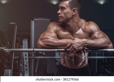 Attractive muscular bodybuilder guy prepare to do exercises with barbell in a gym