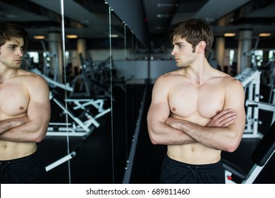 Attractive muscular man admiring his muscles in mirror and checking workout results. Summer Ready Beach Body.
