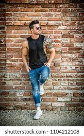 Attractive muscular man standing outdoor leaning against old brick wall, looking to a side