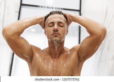 Attractive muscular man taking a shower