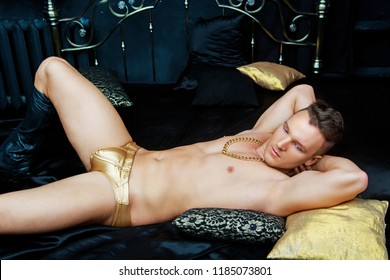 attractive muscular man wearing a golden chain and underwear   in bed with black linen