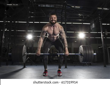 Attractive muscular shirtless athlete doing heavy  deadlift exercise in modern gym.Functional training.Screaming for motivation