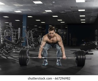 Attractive muscular shirtless athlete doing  deadlifts in modern gym.Functional training.Start position