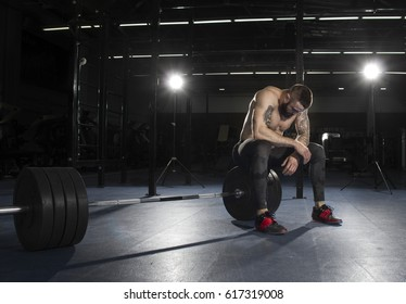attractive muscular shirtless athlete taking the break from heavy deadlift exercise in modern fitness center.Functional training.
