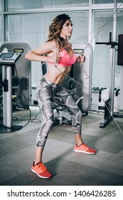 Attractive muscular smiling fitness woman doing hard exercise in modern gym. Power fitness, sport, training, lifestyle