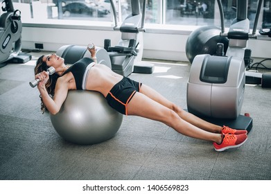 Attractive muscular smiling fitness woman doing exercise with dumbbells and pilates ball in modern gym. Power fitness, sport, training, lifestyle