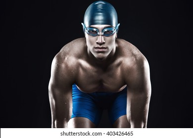 Attractive and muscular swimmer ready to jump into water. Studio shot of young shirtless sportsman on black background. Man with glasses