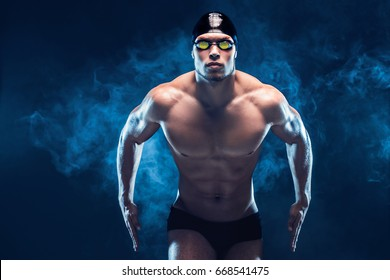 Attractive and muscular swimmer. Studio shot of young shirtless sportsman on black smoke background. Man with glasses.