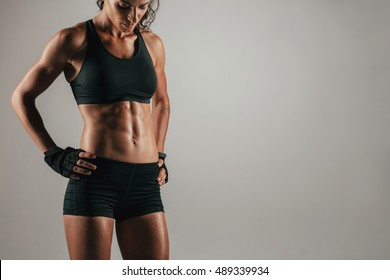 Attractive muscular woman with gloved hands on hips showing off her strong abs over gray background