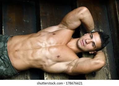 Attractive muscular young man laying on steps of wooden stair, looking at camera, shirtless