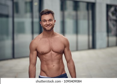 Attractive muscular young man posing shirtless in an urban environment looking at the camera with a warm friendly smile with copy space