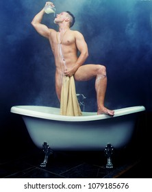 attractive muscular young man taking a bath with milk