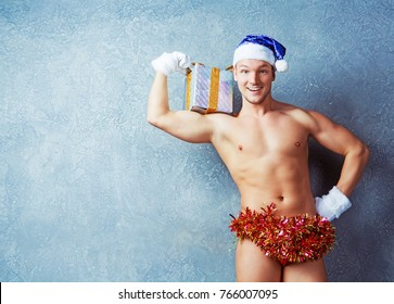 attractive muscular  young man wearing a Santa's hat with Christmas present in the studio