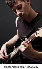 attractive musician with guitar against dark background