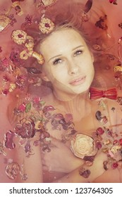Attractive naked girl enjoys a bath  and  petals. Spa treatments for skin rejuvenation