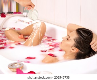 Attractive naked girl enjoys a bath with milk and rose petals.Spa treatment for nutrition and moisturizing skin renewal