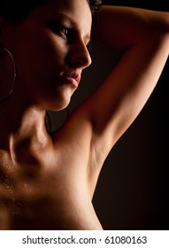 Attractive naked girl with water drops on skin. Over black background