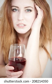 Attractive naked woman in a beauty style pose expressing concern holding a glass of wine