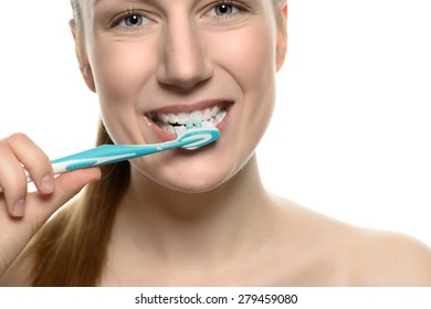 Attractive naked woman brushing her teeth with a toothbrush in a medical, dental care and oral hygiene concept, head and shoulders isolated on white