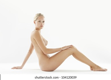 Attractive naked woman isolated on a white background, looking at camera while leaning back on her hand.