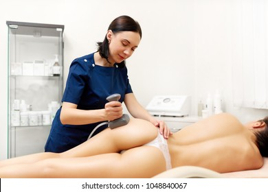 Attractive naked woman lying and enjoying procedure in modern beauty salon. Professional cometologist doing anticellulite massage on buttocks using vela shape, preventing overweight.