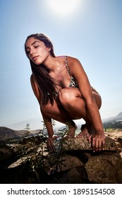 An attractive native American female in a swimsuit sensitivity posing on a rock
