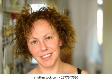 Attractive natural Hispanic woman with curly unruly hair giving the camera a quiet smile on a bad hair day indoors at home