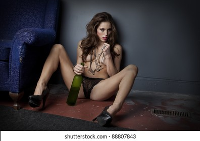 Attractive nearly-naked woman seated on grungy floor holding half empty bottle of wine between her legs.
