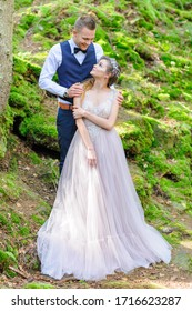 An attractive newlywed couple, a happy and joyful moment. A man and a woman shave and kiss in holiday clothes. Bohemian-style wedding cermonia in the forest in the fresh air.