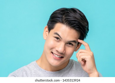 Attractive nice smiling Asian man presenting the concept of Wisely Thinking closeup shot isolated on light blue studio background