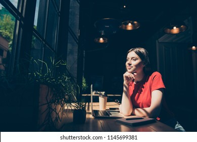 Attractive nice smiling dreamy young girl freelancer student wearing casual sitting in cafeteria, working remotely, drinking coffee, dark interior